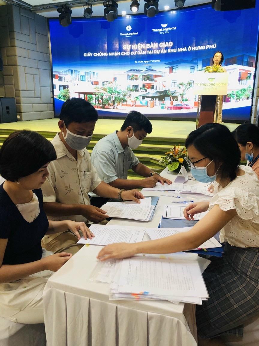 Chuyên viên Công ty CP Hưng Phú Invest làm thủ tục bàn giao GCN cho khách hàng
